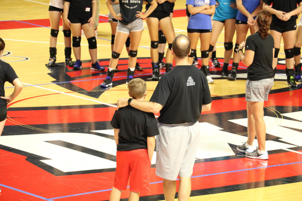 Travis Hudson watches volleyball practice with his son.